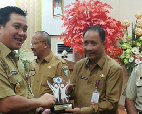 Wagub Drs Steven OE Kandouw saat menyerahkan Penghargaan Kepegawaian Award 2017 kepada Sekot Manado Drs Rum Usulu