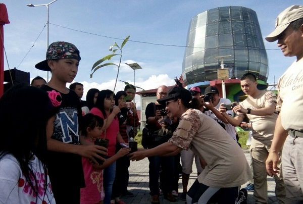 Ny Ruthi Bambang Waskito saat menyerahkan bibit pohon cempaka kepada anak anak jurnalis untuk ditanam di kawasan Godbless Park Manado didampingi suami tercinta Bpk Irjen Pol Drs Bambang Waskito selaku Kapolda Sulut