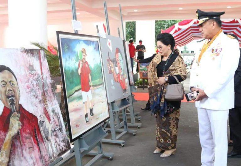 Gubernur Olly Dondokambey SE dan Ketua TP PKK Provinsi Sulut Ibu Ir Rita Maya Dondokambey Tamuntuan melihat pajangan lukisan usai Upacara Penurunan Bendera sore hari